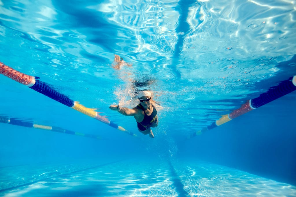 Photo of a girl swimming underwater in a pool.
