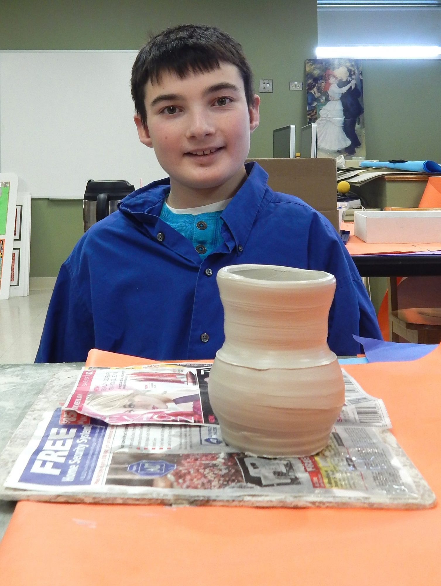 Patrick poses with the pottery he crafted