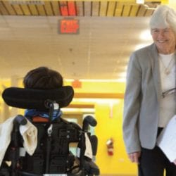 Butch Wallace passing a student in a wheelchair at Cotting School