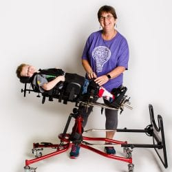 Physical Therapist adjusting a young student in a stander