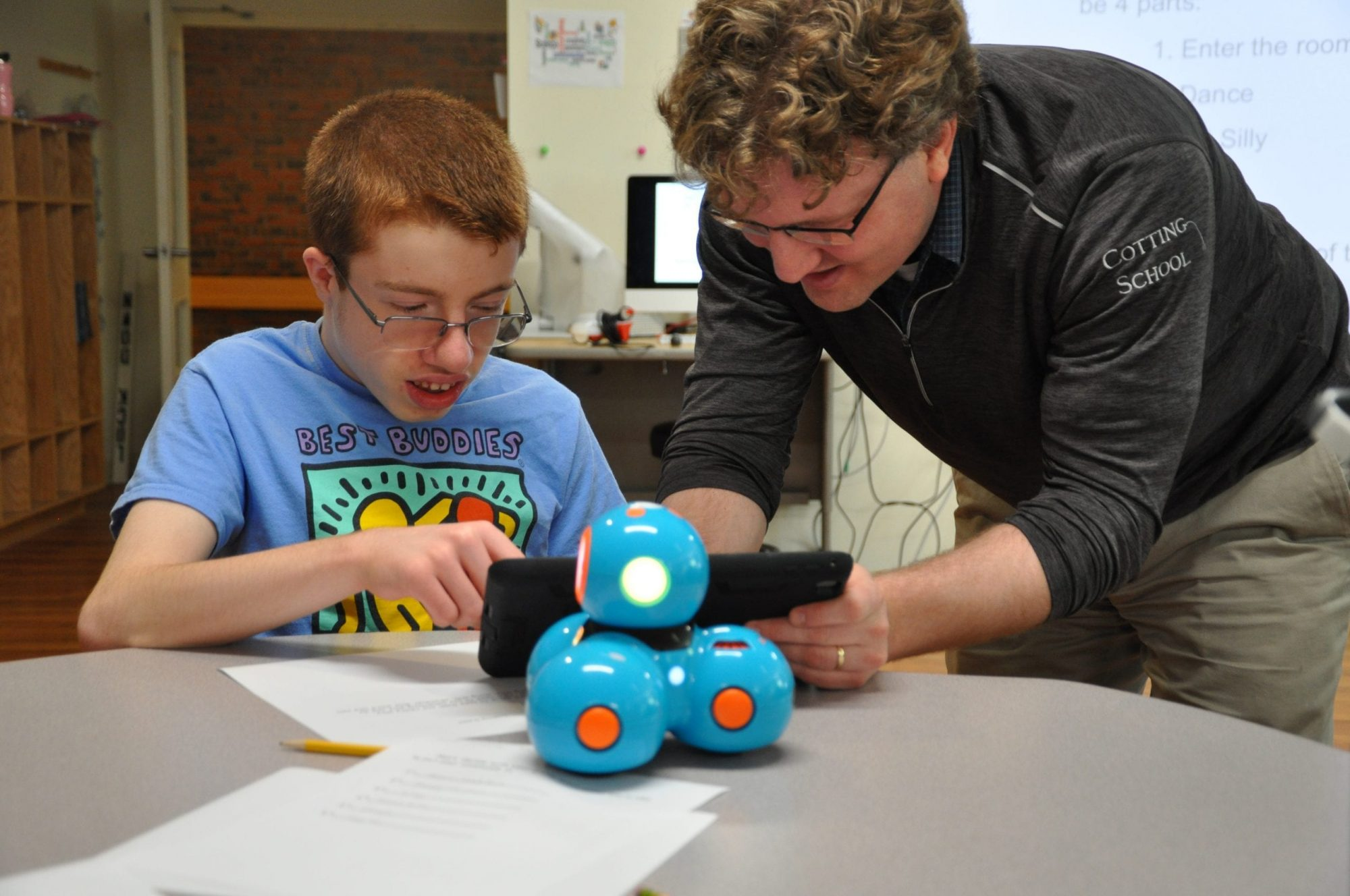 A Cotting School student and a teacher programming a robot